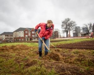 Dr. Rachel Wilson turning soil in a garden